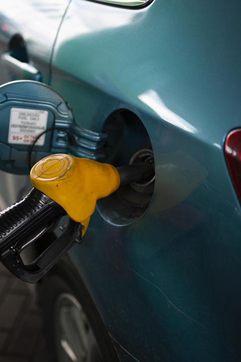 refueling the fuel tank of the vehicle with diesel or gasoline at a filling フォト