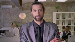 Handsome businessman with beard is standing with arms crossed and watching at Footage