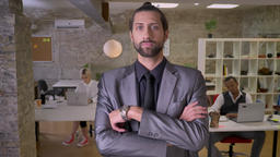 Handsome confident businessman with beard is standing with arms crossed and Footage