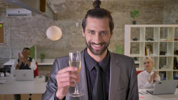 Attractive businessman with beard is standing and holding glass of champagne in Footage