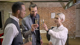 Three multy-ethnic workers dancing in office, clink glasses, drinking champagne Footage