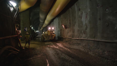 Large construction trucks working inside a tunnel GIF