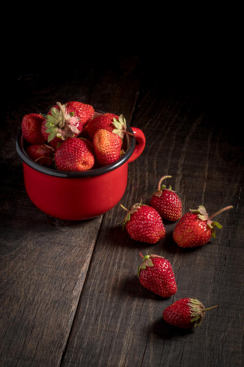 Strawberries in an iron mug on a wooden table フォト