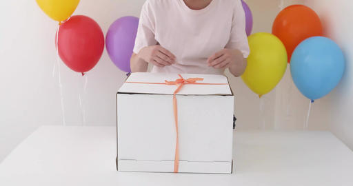 Female hands pulling a red ribbon to open gift box Archivo