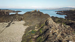 Aerial view of a drone shadow flying over the rocks at Bulls Bay on Anglesey - ビデオ