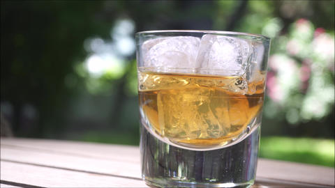 Glass of whisky with ice cubes on the wooden table ビデオ