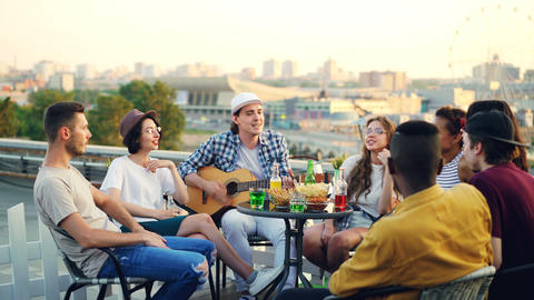 Multiracial group of young people is singing song sitting in circle on roof Footage