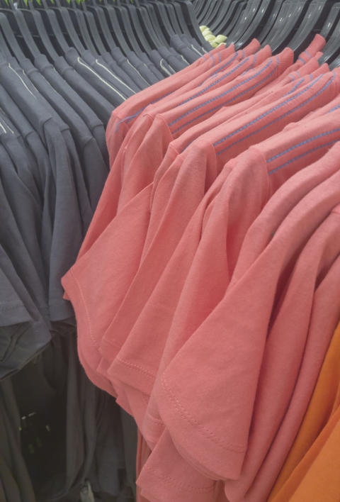 Clothes hanged on a clothes rack in the store フォト