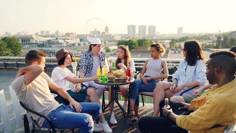 Emotional youth friends are speaking sharing news sitting on rooftop with food Archivo