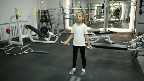 Little girl in the gym engaged with dumbbells Footage