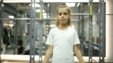 Little girl looks at her muscles Footage