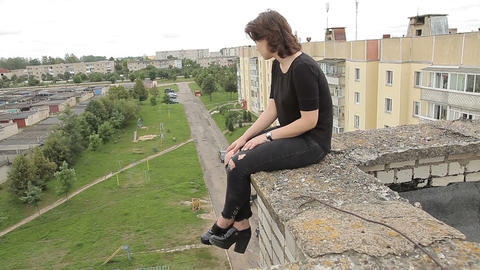 Teen girl sitting on the edge of the roof ビデオ