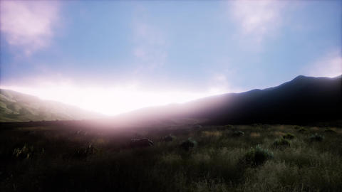 Sunset over a green grassy rocky hills Footage