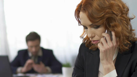 Sad businesswoman talking on the smartphone at workplace, stress, overworking Footage