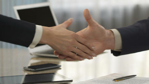 Male and female business partners signing contract and shaking hands, purchase Footage