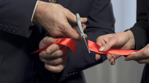 Business partners cutting red ribbon and shaking hands, partnership, agreement Footage