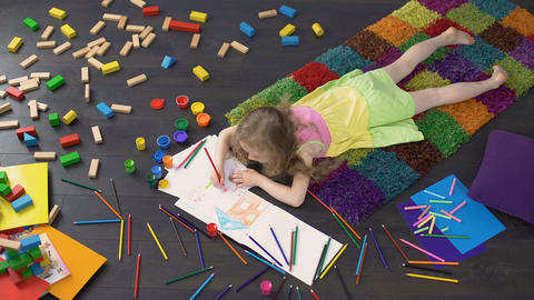 Little curly girl drawing with color pencils on the floor at home, childhood Live Action
