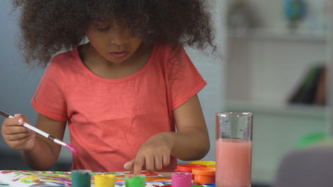 Curly black-haired girl painting with watercolors at art school, art hobby Live Action