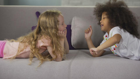 Cute multiracial best friends lying on sofa and having fun, childhood and joy Footage