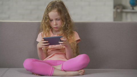 Blond curly-haired child relaxing on sofa and playing on smartphone, addiction ライブ動画