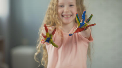 Positive girl showing painted palms into camera and laughing, happy childhood Live Action