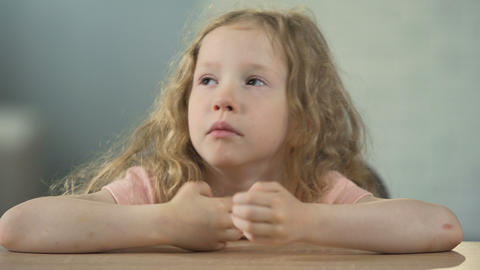 Sad little girl sitting at the table and crying, children's abuse, loneliness Live Action