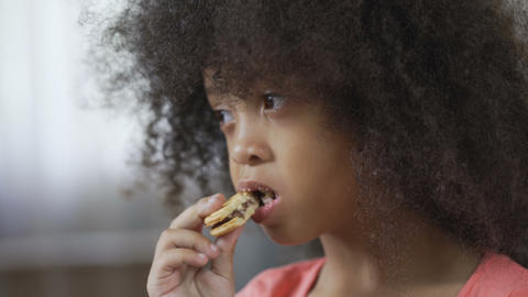 Hungry African American female kid eating cookie with appetite, close-up Live Action