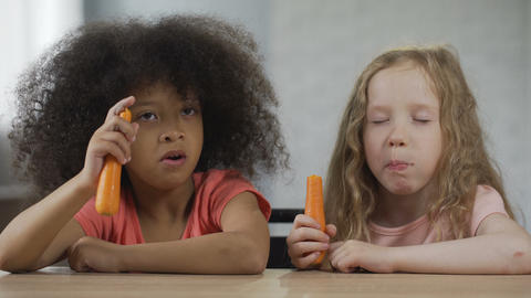 Two pretty little girls sitting at the table and eating carrot with appetite Live Action