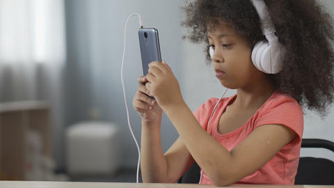 Serious African-American kid wearing headset and watching video on cellphone Footage