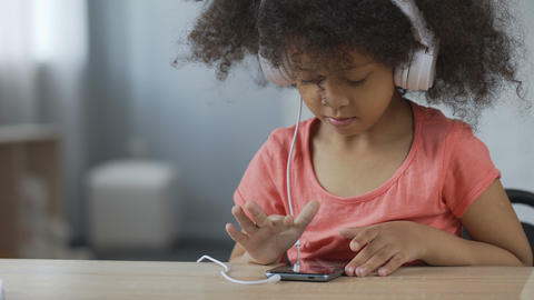 Beautiful child with headset listening to music and viewing photos on cellphone Footage