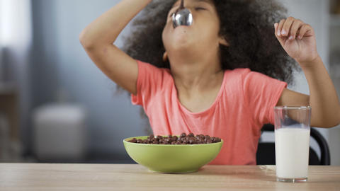 Pretty African American girl eating cornflakes with appetite and drinking milk Live Action