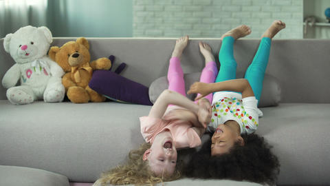 Little multiracial children lying on sofa and having fun at home, childhood Live Action