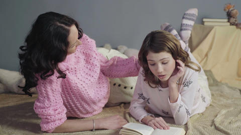 Mom attentively listening her daughter reading bedtime storybook, happy family Live Action