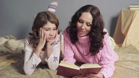 Mother reading aloud interesting storybook to her daughter, family values Live Action