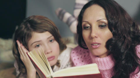 Little girl empathizing with characters from fairy tales, reading with mother Live Action