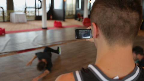 Man filming breakdance performance on his smartphone, leisure activities ビデオ