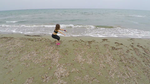 Brunette female athlete training on sandy beach, doing squats, sport and health Footage