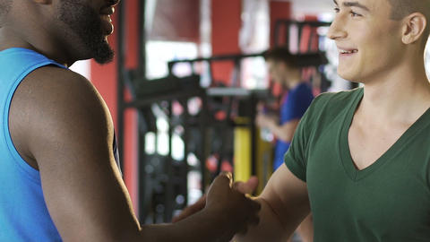 Afro-american and caucasian men shaking hands in gym, international friendship Live Action