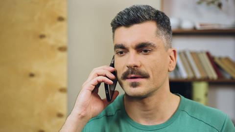 Gray-haired man talking on cellphone at home, making appointment with friends Footage