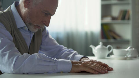 Depressed elderly man sitting at kitchen table, widower suffering loneliness Footage