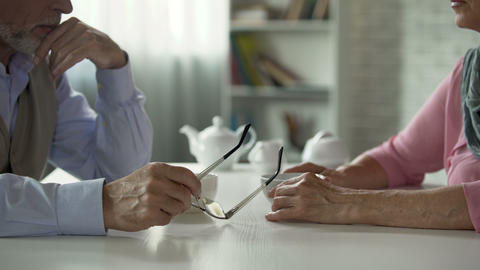 Elderly couple sitting across table over cup of tea, tensed relationship, crisis Live Action