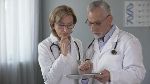 Male doctor showing tablet to his female colleague, electronic medical history Footage