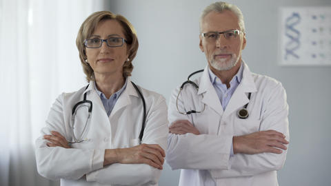 Male and female doctor looking at camera crossing arms, advertisement, guarantee Footage