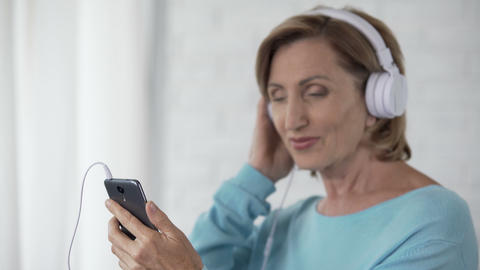 Female pensioner in headphones listening to song on mobile phone and dancing Footage