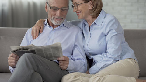 Old man reading newspaper, woman putting arm around his shoulders, gentleness Footage