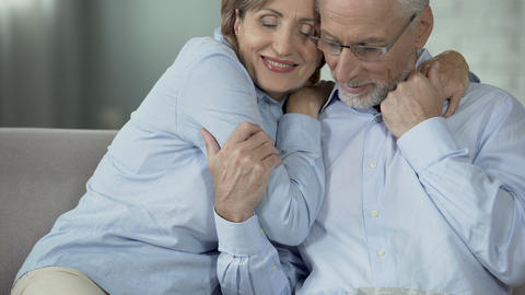 Retired female hugging husband who is reading newspaper, happy elderly couple Footage