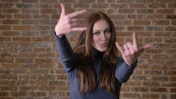 Brown hair girl is watching at camera, showing like sign, rock sign Footage