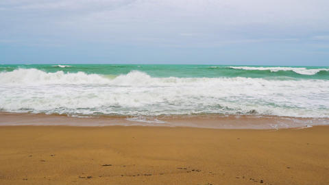 slow motion, the waves are slowly breaking against the sandy tropical beach GIF