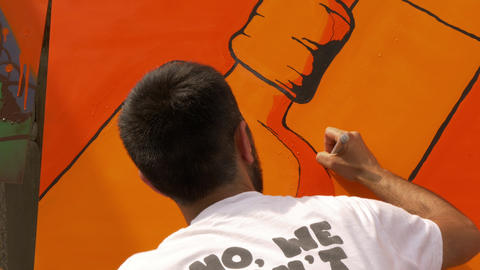 Plovdiv, Bulgaria, June 2017 - Graffiti artist drawing orange painting exterior Footage