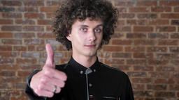 Young caucasian man with curly hair showing thumbs up into camera and smiling Footage